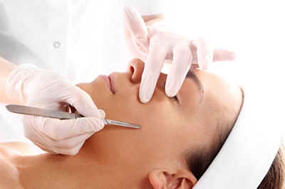 A woman undergoing dermaplaning treatment